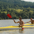 Kayaking sporty men on river sunshine - Stock Photo