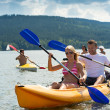 Smiling couple rowing kayak sunshine - Stock Photo