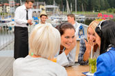 Gossiping women sitting at harbor bar — Stock Photo