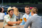 Three male friends drinking beer outdoor terrace — Stock Photo