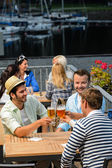 Three men drinking beer at terrace bar — Stock Photo