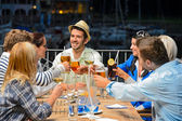 Young friends clinking glasses night restaurant — Stock Photo