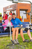 Smiling couple sitting and waiting on chair-lift — Stock Photo