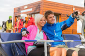 Cheerful couple sitting chair lift man pointing — Stock Photo