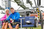 Young couple sitting chair lift waiting departing — Stock Photo