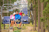 Carefree couple traveling by chair lift wood — Stock Photo