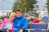 Hugging young couple sitting on chair lift — Stock Photo