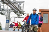 Couple getting on bicycles chair lift trip — Stock Photo