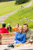 Young tourists drinking refreshments resting wooden bench — Stock Photo