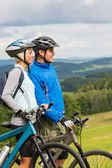 Smiling cyclists watching scenic view with bikes — Stock Photo