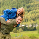 Couple having piggyback ride outside green nature — Stock Photo