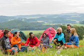 Sitting camping friends with tents and landscape — Stock Photo