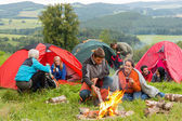 Sitting by campfire friends in tents chatting — Stok fotoğraf