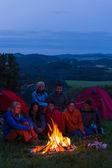 In dark camper friends sitting around fire — ストック写真