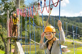 Woman climbing on rope ladder adrenalin park — Stock Photo
