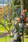 Smiling man climbing in adventure park — Stock Photo