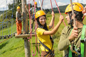 Young couple in safety equipment adventure park — Foto de Stock