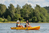 Happy girls kayaking on sunny day — Stock Photo