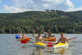 Waving cheerful friends in kayaks summer — Stockfoto
