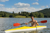 Sporty man in kayak with oar summer — Stock Photo