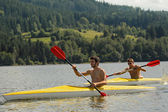 Kayaking sporty men on river sunshine — Stock Photo