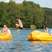 Young man jumping into water paddle boat — Foto Stock