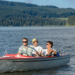 Young men sitting in motorboat scenic landscape — Stock Photo