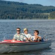 Young men sitting in motorboat scenic landscape - Stock Photo