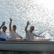 Waving young men silhouette driving powerboat — Stockfoto