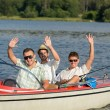Cheerful young men sitting in motorboat — Stock Photo #23390866