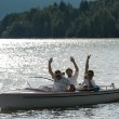 Waving men sitting in motorboat back lit - Stock Photo