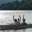 Waving men sitting in motorboat back lit — Stock Photo #23390876