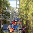 Young couple sitting on chairlift forest - Foto Stock