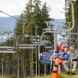 Waving young people sitting on chairlift - Stock Photo