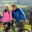 Cheerful cyclist couple with mountain bikes — Stock Photo