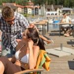 Talking young couple at beach bar — Stock Photo