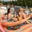 Young women lying on deckchair applying sunscreen - Stock Photo