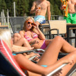 Постер, плакат: Women sunbathing on deckchair guys drinking beer