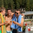 Постер, плакат: Young laughing guys in swimsuits drinking beer