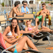 Chatting girls lying on deckchair sunbathing - Stock Photo