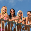 Beautiful women in bikinis smiling with drinks — Stock Photo