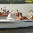 Stock Photo: Waving friends sitting in motorboats summertime