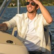 Young man navigating powerboat sunny - Stock Photo