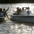 Stock Photo: Silhouette of young friends in motorboats