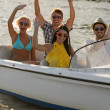 Waving young sitting in motorboat — Stock Photo #23391120
