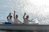 Waving young men silhouette driving powerboat — Stock Photo