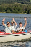 Cheerful young men sitting in motorboat — Stock Photo