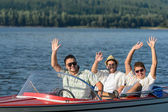 Cheerful young guys partying in speed boat — Stock Photo