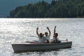 Waving men sitting in motorboat back lit — Stock Photo