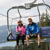 Young couple sitting on chairlift — Stock Photo